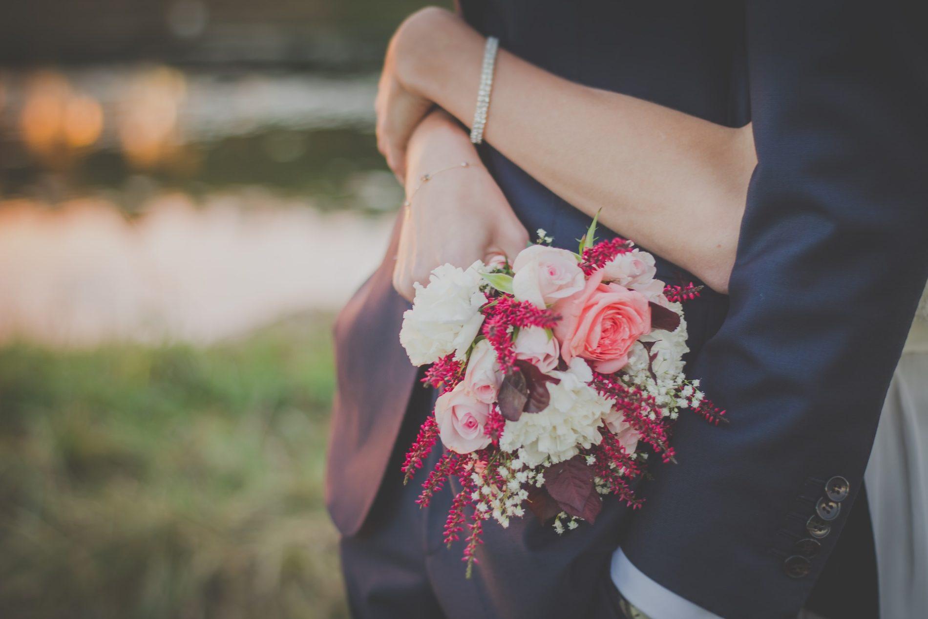 couple de mariés s'enlassant avec bouquet de mariage